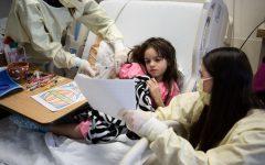 Boston, MA -- 04/13/16 -- Elaine Klingensmith, a teacher with Education Inc., tutors Christiana Silva, 6, while a nurse adjusts her I.V., at Boston Childrens Hospital on April 13, 2016, in Boston, Massachusetts. (Kayana Szymczak for STAT)